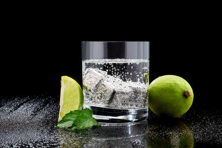 Glass of Soda or Coctail with steel cooling cubes on dark glass background