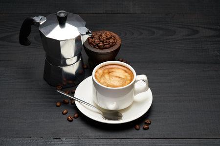 Cup of espresso coffee and mocha coffee maker on dark wooden background Standard-Bild