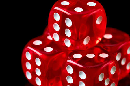 Red casino dice isolated over black reflective background