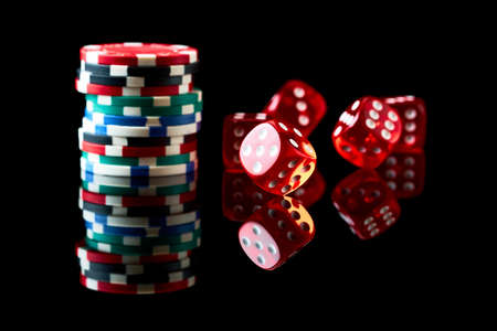 Red casino dice and chips isolated over black reflective background Stock Photo