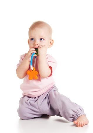 teething: Teething blond baby bites colored toy on white background Stock Photo