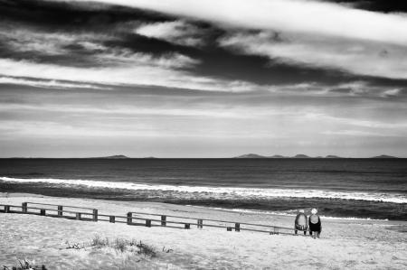 Dos personas de edad avanzada en la playa con vistas al mar en otoño Foto de archivo - 24094764