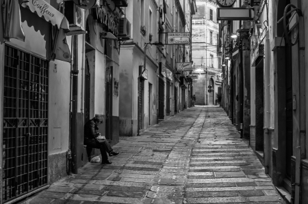 black and white photography: Alley of the old city with an elderly woman who knits