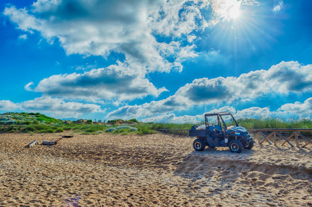 Black quad on the sardinian beach of Porto Ferro in a cloudy morning of summer Stock Photo