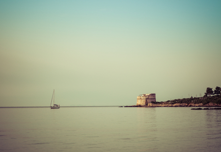 moored sailboat near an ancient tower in a summer morning in Sardinia 스톡 콘텐츠