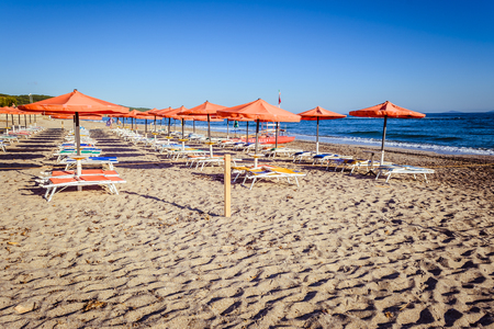 Rows of orange umbrellas on the deserted beach in the morning
