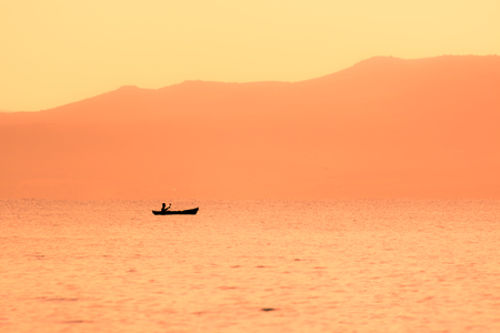 kayak sailing in the coast at sunset