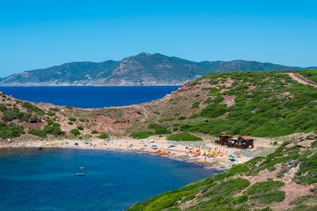 Landscape of the sardinian beach of Porticciolo, with ancient tower on the coast, in summer