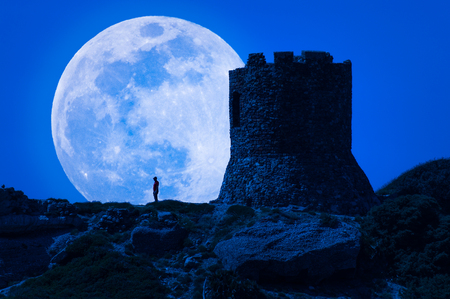 Silhouette of man and ancient tower under super moon