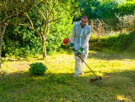 Gardener wearing white suit using a trimmer in a meadow, in a sunny morning of spring Archivio Fotografico