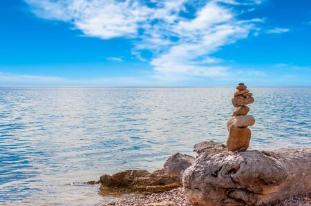 Stacked stones on the coast in a sunny and cloudy day Stockfoto