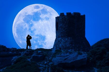 Silhouette of a kissing couple under super moon