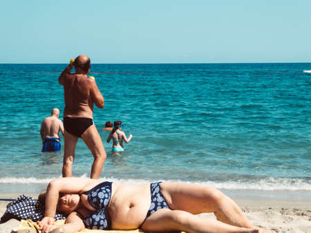 people on the beach in summer with old white man working out Foto de archivo