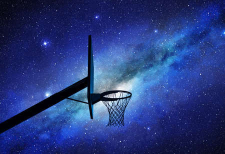 Basketball hoop silhouette at night with milky way in background Foto de archivo