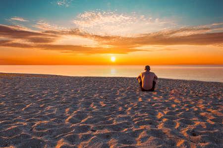 Shirtless man sitting on the beach