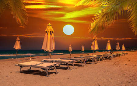 row of umbrellas and deck chairs on the beach at sunset Foto de archivo