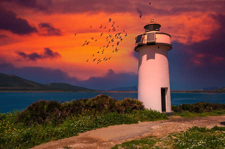 Lighthouse on the sardinian coast at sunset with dramatic red sky - Maristella, Sardinia Foto de archivo