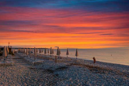 rows of closed umbrellas on the beach at dramatic colorful sunrise Foto de archivo