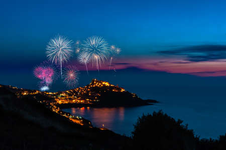 Landscape of city of castelsardo by night with fireworks Foto de archivo