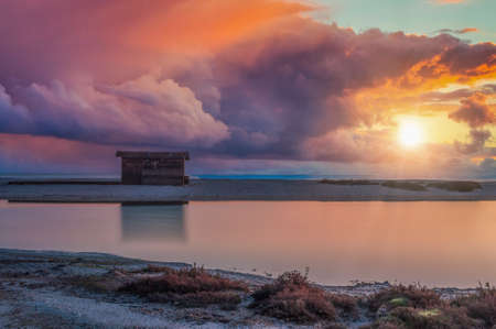 wooden shed by the sea at dawn with dramatic cloudy sky and sun flare