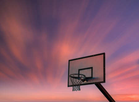 Isolated basketball hoop at sunset with long exposure dramatic red sky