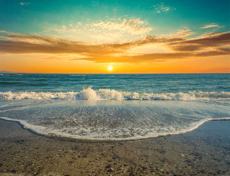 View of sea water foam on the beach at dramatic sunset