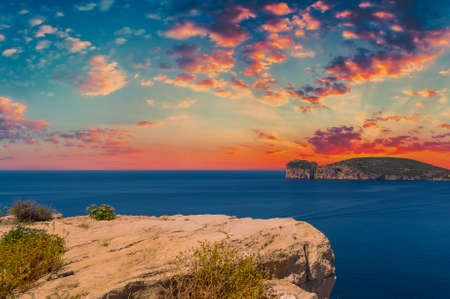Landscape of the coast of Capo Caccia, in Sardinia, at dramatic sunset with red clouds