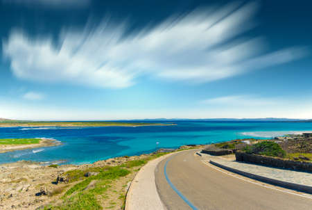 Landscape of La Pelosa beach in a sunny day with long exposure sky and clouds