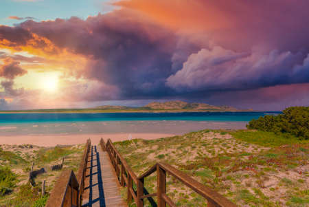 Landscape of wooden footbridge to the sea at dramatic sunset