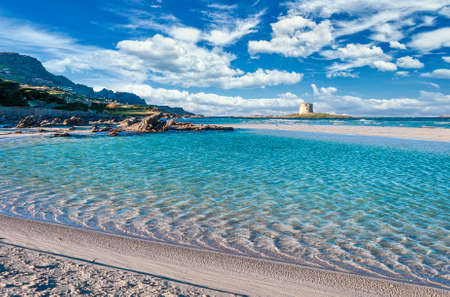 landscape of La Pelosa beach, in Stintino, in a sunny and cloudy day, with ancient tower and crystal clear water
