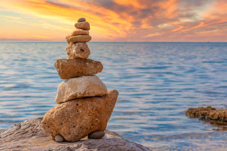 Stone stacking on the coast at sunset with dramatic sky
