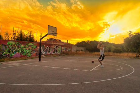Basketball player shooting and training in city playground at sunset