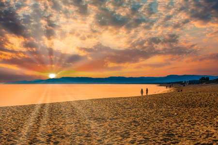 seascape on the beach with dramatic sky and sun lens flare at sunset Foto de archivo