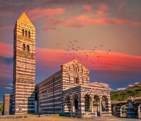 View at the Basilica Holy Trinity of Saccargia - Sardinia - Italy at sunset with dramatic sky and red clouds Foto de archivo
