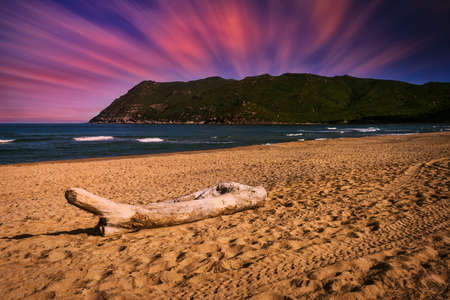 Landscape of beach at dramatic sunset with long exposure clouds and sky