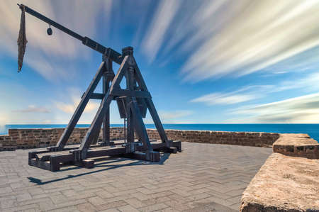 ancient catapult on the ramparts of Alghero in a sunny day of spring with long exposure clouds