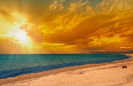 Landscape of beach at sunset with dramatic cloudy red sky and sun lens flare Foto de archivo