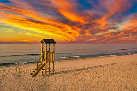 lifeguard tower on the beach with a dramatic red sunset Foto de archivo