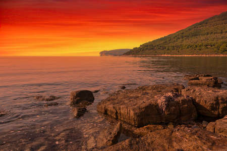 Landscape of Capo Caccia coast, in Sardinia, at dramatic red sunset Foto de archivo