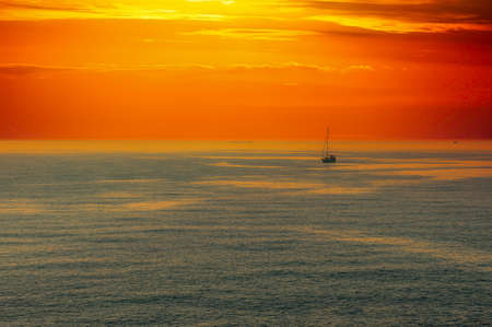 seascape at sunset with dramatic red sky and sail boat