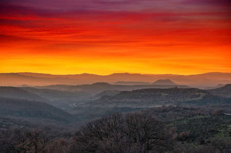 Landscape of mountains at sunset with dramatic red and orange sky