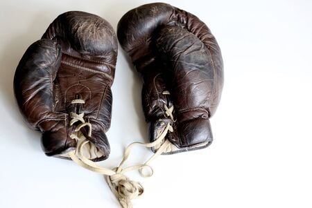 Old vintage boxing gloves made of aged brown leather close up taken on the white background with copy space around. Boxing time memories concept 版權商用圖片