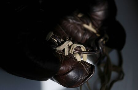 Old vintage boxing gloves made of aged brown leather close up taken on the white background. Boxing time memories concept. Vintage sports equipment concept