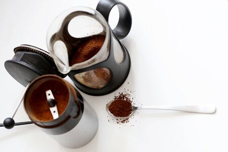 Coffee break concept. Tea spoon full of ground coffee arabica, french press coffee maker and electric coffee grinder are on the white background flat lay and close up taken