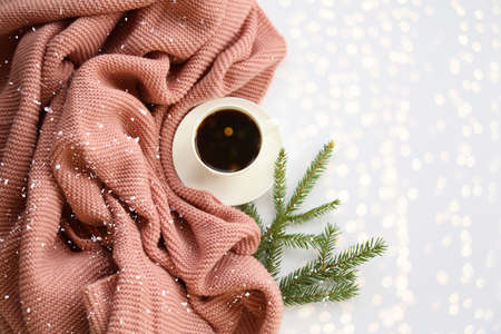 White ceramic coffee cup with hot black coffee on the cute knitted pink scarf and fir branches background close-up. Sweet home winter time concept
