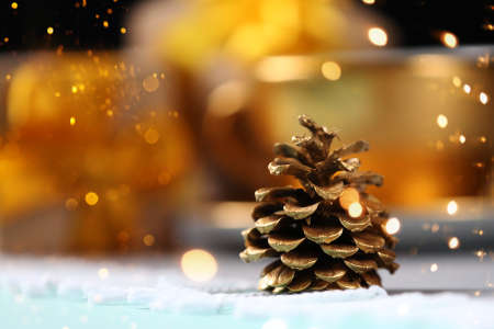 Golden pine cone like small Christmas tree on blurred gift boxes and coffee cup background. Shining sparkles and magic light. New Year background.