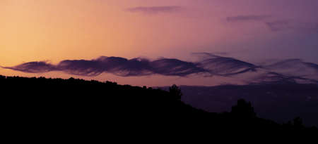 Beautiful dramatic sky with spiral purple clouds on dark mountains background, horizontal banner Stock Photo