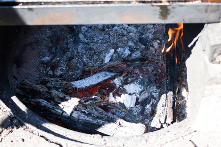 Small summer camp fire and embers in fire place