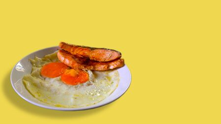 Fried egg and salmon In a white plate with yellow background. Reklamní fotografie
