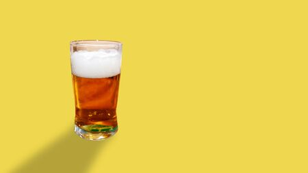 Beer glass on a yellow background.